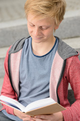 Teenage boy studying reading book