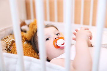 baby with pacifier in white bed