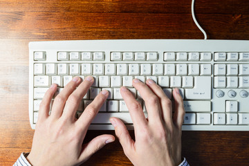 Woman hands typing on a white keyboard on wooden background
