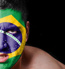 Portrait of angry man with painted flag of Brazil