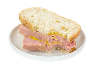 Bitten ham sandwich on small plate