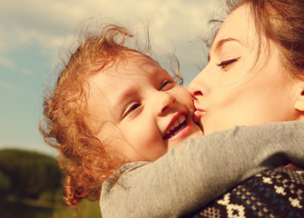 Mather kissing her happy smiling daughter outdoors summer