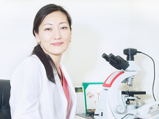 Portrait of young asian girl doctor looking to microscope in lab