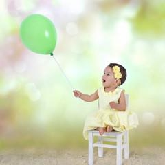 Staunendes Kleinkind mit Luftballon