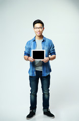 man showing tablet computer screen on gray background