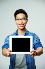 Young happy asian man showing tablet computer screen