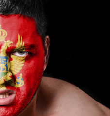 Portrait of angry man with painted flag of Montenegro