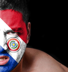 Portrait of angry man with painted flag of Paraguay
