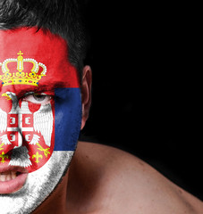 Portrait of angry man with painted flag of Serbia
