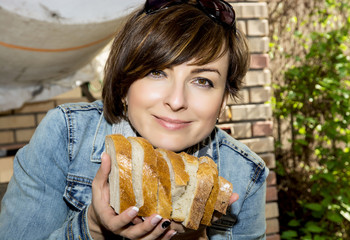 Positive woman offering fresh sliced bread