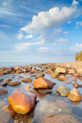 Blue sky and stones in the ocean. The Baltic Sea coast, Poland.