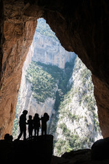 Silhouette children in a Colomera cave, Montsec mountain, Spain
