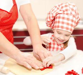 Little girl and grandmother cut dough with form  for cookies
