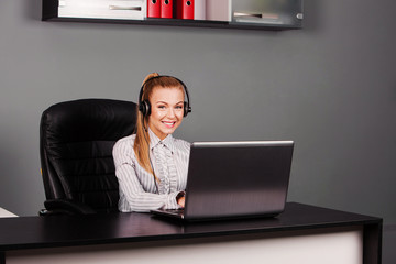 smiling female helpline operator with headphones