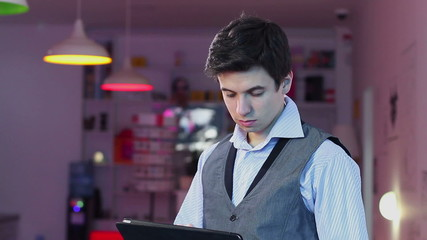 Man reading tablet pc, standing businessman HoReCa business