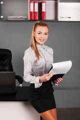 business woman  the office with papers in hand