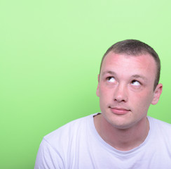 Portrait of man thinking and looking up against green background
