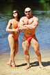 Attractive fitness couple posing on a beach