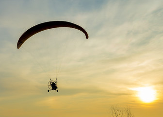 Silhouette paramotor in sunset.