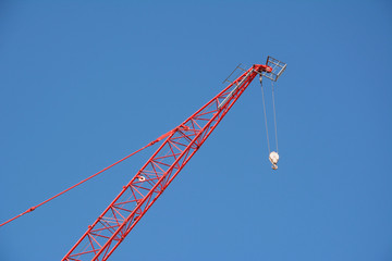 Red crane boom against a blue sky