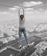 A woman hanging on a rope over the city