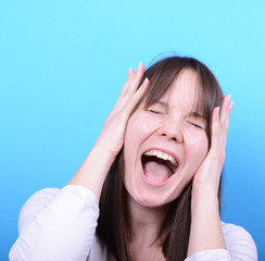 Portrait of girl screaming against blue background