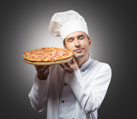 Portrait of a chef with closed eyes smelling pizza