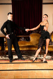 Young dance couple preforming latin show dance in ancient ballro poster