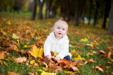 Little girl in autumn Park with leaves