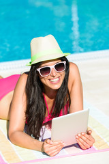 Womanwith tablet reading on summer vacation
