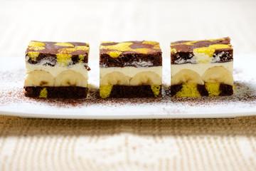 Zweifarbiger Kuchen gefüllt mit Bananen und Sojaschlagcreme