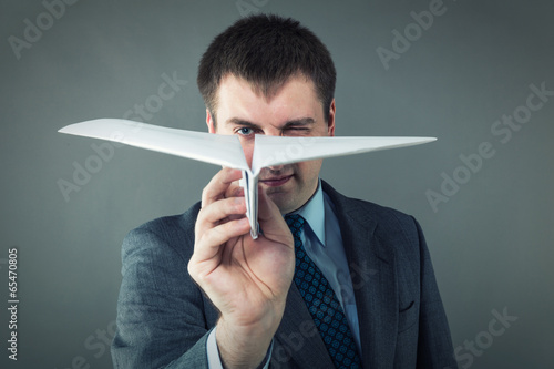 Businessman with paper plane in studio - 65470805