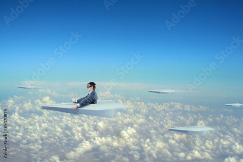 Businessman flying on paper plane - 65470825