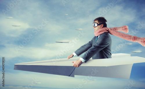 Leinwanddruck Bild Businessman flying on paper plane