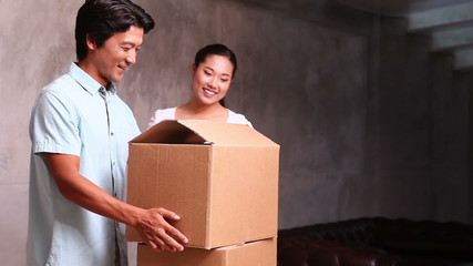 Young asian couple unpacking moving boxes