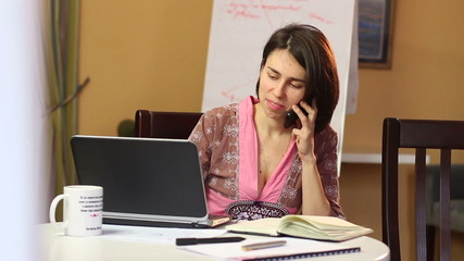 Woman talking over mobile phone in cafe, laptop browsing dating