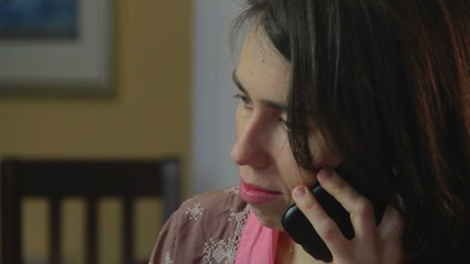 Close-up sad single woman talks phone, breaking relationships