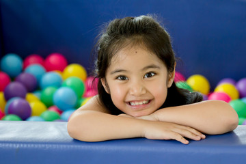 Happy Asian child playing at kindergarten with colorful balls
