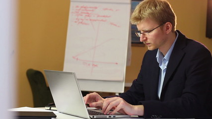 Working blond businessman in glasses with laptop printing e-mail