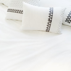 Elegant white bed linen with pillows