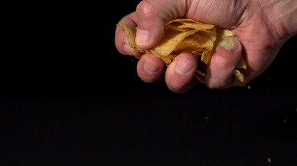 Hands crushing potato chips on black background