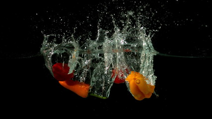 Chili peppers falling in water on black background