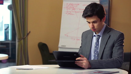 Business man reading news on tablet PC, financial updates index