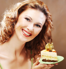 young woman holding up a delicious piece of cake