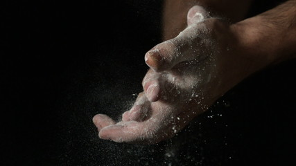 Bakers hands rubbing flour off on black background