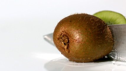 Kiwi being sliced in half on wet white background