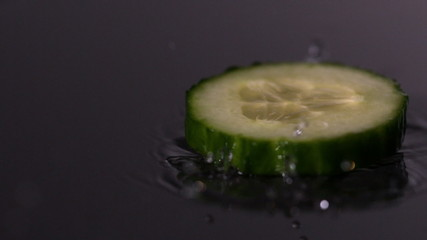 Courgette slice falling on wet black background