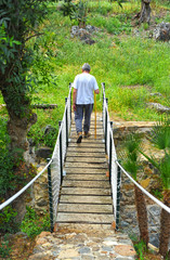 Man crossing the small wooden bridge, walkway