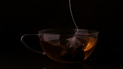 Teabag dunking into glass cup