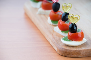 Simple snack canape with tomato, mozzarella and basil